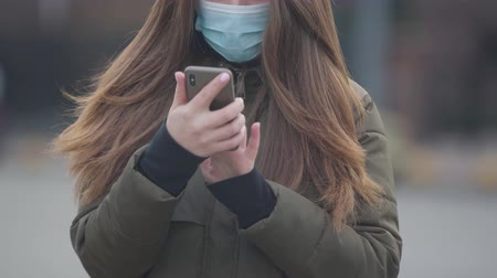 mortality : Close-up of unrecognizable young woman in protective mask using smartphone. Brunette woman standing on city street reading news about coronavirus. Medicine, healthcare, hazard.