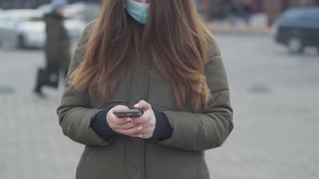 screening : Unrecognizable brunette woman wearing protective mask standing on city street. Young woman typing on the phone. Coronavirus, isolation, global hazard.