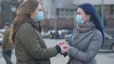 mortality : Close-up of two young women in protective masks standing on city street and talking. Brunette girl and her female friend with blue hair discussing last news about coronavirus. Danger, epidemic. Stock Footage