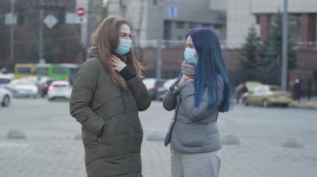 fájó : Side view of two anxious women with sore throat in protective masks talking on city street. Friends discussing symptoms of global virus. Danger, coronavirus, hazard.