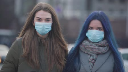 mortality : Portrait of two women in protective masks looking at camera as standing on city street. Young female friends using safety masks for protection against coronavirus. Pandemic, epidemic, hazard. Stock Footage