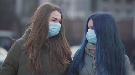 vaccino : Two young women in protective masks looking at each other, signing and looking at camera. Close-up of female friends with virus symptoms standing on city street. Global problem, coronavirus, pandemic. Filmati Stock