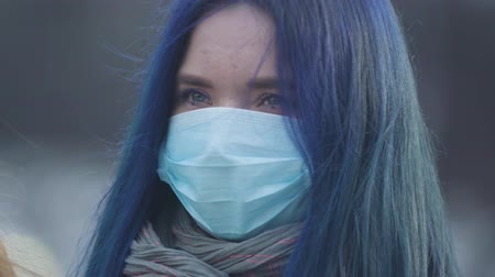 kockázat : Close-up face of young woman with blue hair and blue eyes wearing protective mask. Portrait of woman standing on city street during epidemic outbreak. Hazard, danger, pandemic, coronavirus.