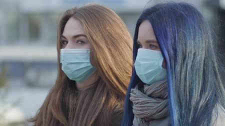 mortality : Side view close-up of two anxious women in protective masks looking away. Women standing on city street. Focus changes from blue-haired girl to brunette woman. Global danger, hazard, virus.