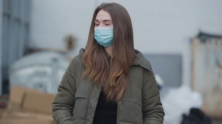 mortality : Portrait of young woman in protective mask looking at camera. Pretty brunette woman protecting against global pandemic virus. Healthcare, medicine, coronavirus.