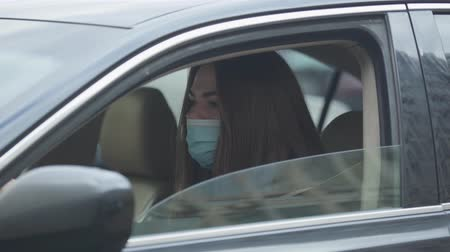 mortality : Side view portrait of young woman in protective mask sitting in car and coughing. Young woman with symptoms of disease sitting on drivers seat. Coronavirus, virus, global hazard.