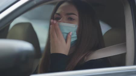 mortality : Close-up of coughing young woman sitting on drivers seat wearing protective mask. Portrait of tired brunette woman with illness symptoms. Healthcare, medicine, pandemic. Stock Footage