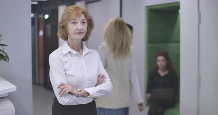 analista : Portrait of serious middle aged Caucasian woman standing with hands crossed in open space office, turning to reception desk and taking papers. Confident CEO at workplace. Cinema 4k ProRes HQ. Archivo de Video