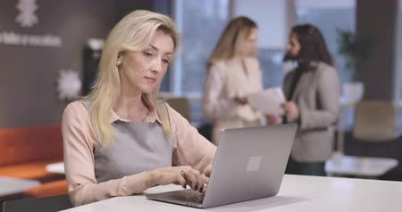 analista : Portrait of beautiful Caucasian woman typing on laptop keyboard, looking at camera and smiling. Portrait of young successful CEO at workplace. Businesswoman, manager. Cinema 4k ProRes HQ.