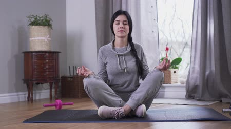 acalmar : Calm brunette Caucasian woman sitting with eyes closed on yoga mat. Young woman calming down after hard day. Lifestyle, tranquility, relaxation. Vídeos