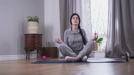 закрытыми глазами : Camera approaching to confident brunette Caucasian woman meditating at home. Young woman sitting on yoga mat with eyes closed and crossed legs. Tranquility, lifestyle, relaxation.