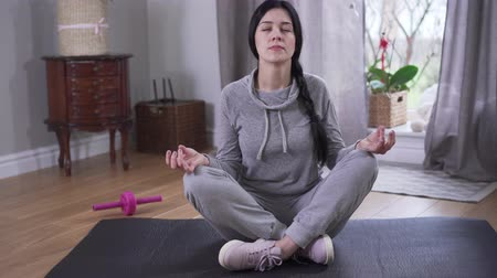 закрытыми глазами : Meditation on confident young woman indoors. Brunette Caucasian woman with closed eyes sitting on yoga mat and thinking. Camera moving around from right to left. Yoga, lifestyle, resting. Стоковые видеозаписи