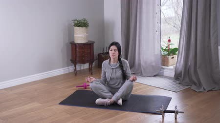 закрытыми глазами : Top view long shot of relaxed Caucasian woman meditating indoors. Beautiful young woman practicing yoga at home. Relaxation, tranquility, lifestyle.