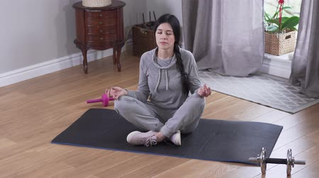 закрытыми глазами : Top view of young brunette Caucasian woman practicing yoga indoors. Confident relaxed woman meditating at home. Resting, tranquility, lifestyle. Стоковые видеозаписи