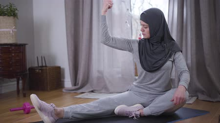 emelt : Cheerful Muslim woman boasting muscles and looking at camera. Young smiling woman in hijab and sportswear sitting at home on yoga mat with hand raised. Sport, lifestyle, strength. Stock mozgókép