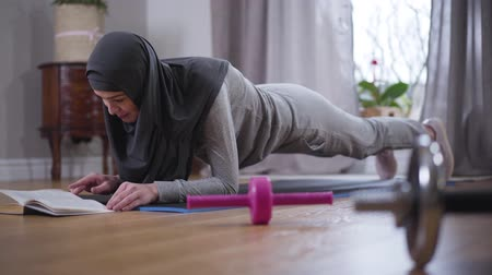 yoğunlaşma : Strong Muslim woman in hijab and sportswear doing sport planc exercise and reading book. Confident young woman practicing sport and hobby at home. Leisure, lifestyle, enjoyment. Stok Video