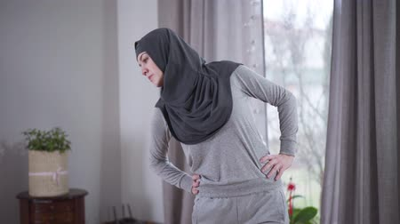 inspirar : Workout of young Muslim woman at home. Positive woman in hijab bending aside indoors. Lifestyle, sport, exercising, health and beauty.