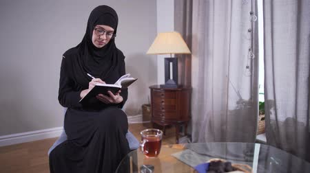 головной платок : Concentrated Muslim woman in eyeglasses writing at home. Successful modern female writer in hijab creating new best seller. Creativity, lifestyle, author.
