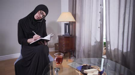escritor : Young successful Muslim woman talking on the phone and writing. Confident woman in hijab working on new book. Inspiration, creativity, lifestyle.