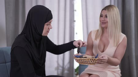 bolinhos : Positive blond Caucasian woman treating Muslim friend with sweets. Two women from different cultures drinking tea and talking indoors. Friendship, diversity, cultural difference, lifestyle. Stock Footage