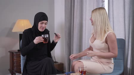 hoşgörü : Positive Muslim woman in traditional black hijab drinking tea with Caucasian female friend. Friendship of young women representing diverse cultures. Modern society, lifestyle, tolerance.