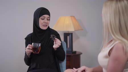 hoşgörü : Portrait of happy Muslim woman in hijab drinking tea with cookie and talking with blond Caucasian friend. Friendship of two modern women from diverse cultures . Communication, community, social.