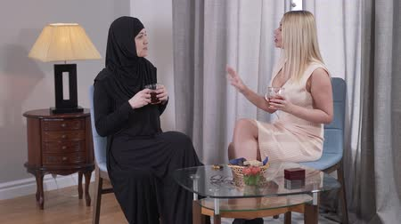 conservative : Side view of two different women drinking tea and talking at home. People from Caucasian and Muslim cultures spending free time together. Cultural diversity, tolerance, lifestyle.