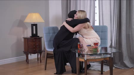 ragaszkodás : Long shot of Muslim and Caucasian women sitting at the table at home and hugging. Best friends from different cultures resting indoors. Cultural variety, diversity, tolerance.
