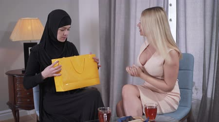 hoşgörü : Conservative Muslim woman getting present from Caucasian modern friend. Young lady in hijab taking out candid dress with sparkles. Cultural difference, diversity, discrepancy. Stok Video