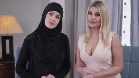 hoşgörü : Caucasian and Muslim women looking at camera and smiling. Blond modern woman in candid dress and Muslim lady in black hijab posing indoors. Cultural diversity, tolerance.