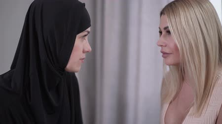 hoşgörü : Close-up faces of two women looking at each other. Portrait of modern Caucasian gorgeous lady and conservative Muslim woman in hijab. Camera moving around from left to right. Stok Video