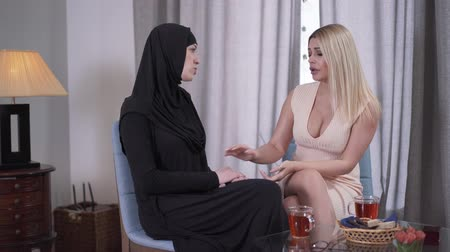 İslamiyet : Anxious women sitting indoors and talking. Caucasian modern lady calming down her Muslim friend in traditional hijab. Diversity, friendship, tolerance. Stok Video