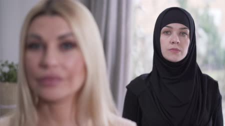 szerény : Focus changes from modest Muslim woman in hijab to face of young modern Caucasian lady looking at camera. Depiction of diversity of modern society. Tolerance, lifestyle, beauty.