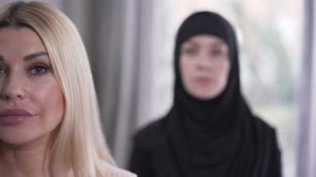hoşgörü : Focus changes from face of modern Caucasian blond woman to young Muslim woman looking at camera. Portrait of two different women. Cultural diversity in modern society.