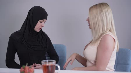 conservative : Modest Muslim woman in hijab talking with blond Caucasian friend criticizing her outfit. Conservative lady and modern girl discussing cultural differences. Tolerance, communication, lifestyle.