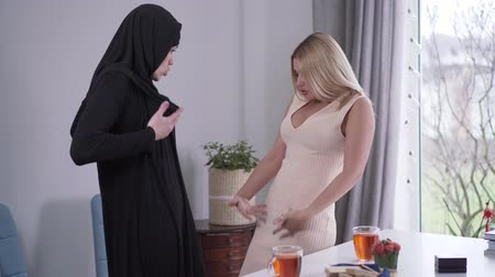 conservative : Obedient Muslim woman in hijab scolding female Caucasian friend for her candid dress. Beautiful blond woman arguing with conservative friend regarding outfit. Cultures conflict, diversity, tolerance.