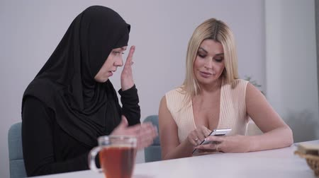 conservative : Portrait of confident young Caucasian woman showing smartphone to Muslim friend. Conservative woman in hijab closing face with hands, her modern friend smiling. Diversity, modern community, lifestyle. Stock Footage