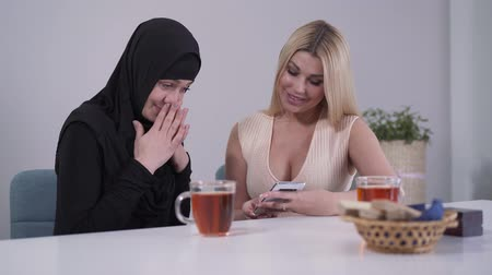 conservative : Shy Muslim woman and confident Caucasian lady looking at smartphone screen and smiling. Multicultural female friends resting indoors and using social media. Friendship, variety, tolerance. Stock Footage