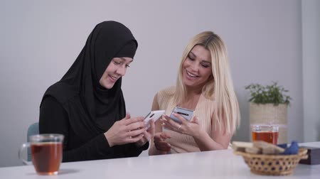 conservative : Happy Caucasian and Muslim women using smartphones and laughing. Cheerful female friend from different cultures spending weekends indoors. Tolerance, diversity, multicultural friendship.