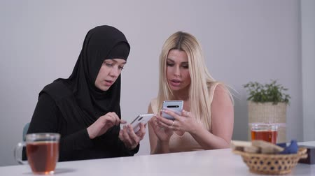 conservative : Two young women from different cultures using social media on smartphones. Muslim and Caucasian lady sitting at the table indoors and talking. Communication, multicultural friendship, tolerance. Stock Footage