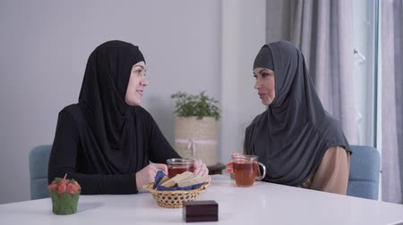 conservative : Two Muslim women in hijabs sitting at the table with tea and talking. Positive young ladies gossiping indoors. Eastern culture, communication, friendship.
