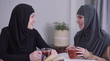 conservative : Close-up of two happy Muslim women talking and laughing indoors. Female friends sitting at the table with tea and gossiping. Culture, friendship, communication.