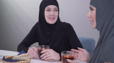 conservative : Close-up portrait of young Muslim woman in black hijab smiling and talking with friend. Two women communicating indoors and drinking hot tea. Friendship, lifestyle.