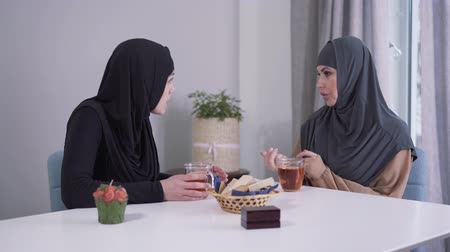 disputa : Portrait of two Muslim women arguing indoors. Beautiful eastern ladies in hijabs sitting at the table at home and talking. Conflict, discussion, misunderstanding.