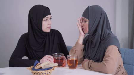 conservative : Modest Muslim woman in hijab calming down her modern-looking female friend. Young lady comforting and hugging crying friend. Friendship, communication, support.