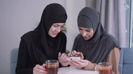 conservative : Modern-looking Muslim woman showing smartphone screen to modest friend in hijab. Two women reacting emotionally at social media. Modern technologies, communication, lifestyle.