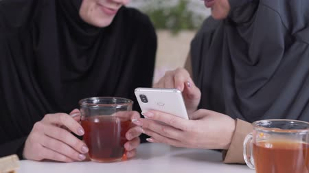 conservative : Close-up of two unrecognizable Muslim women using smartphone, talking and smiling. Coexistence of traditional culture and modern society. Lifestyle, social media, Internet.