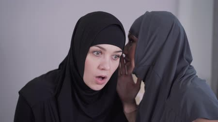 hoşgörü : Portrait of young Muslim woman in hijab listening to friend whispering on her ear. Surprised woman covering mouth with hand. Two female friend gossiping. Lifestyle, traditional culture.