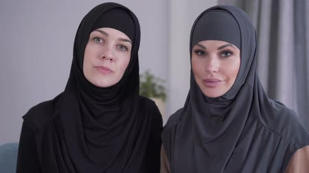 conservative : Close-up of conservative and modern-looking Muslim women looking at camera and smiling. Two different ladies from one culture posing indoors. Lifestyle, beauty, diversity. Stock Footage