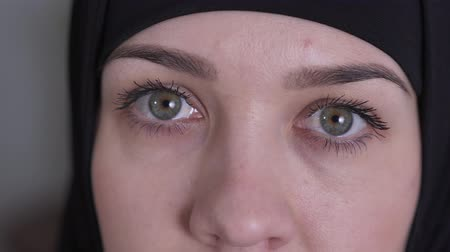 conservative : Extreme close-up of hazel eyes of sad Muslim woman in traditional black hijab. Portrait of beautiful young eastern lady looking at camera. Beauty, lifestyle. Stock Footage